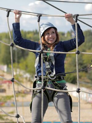 Kari Byron climbing a rope fence.